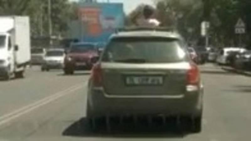 В Бишкеке ребенок едет, высунувшись из люка машины. Видео
