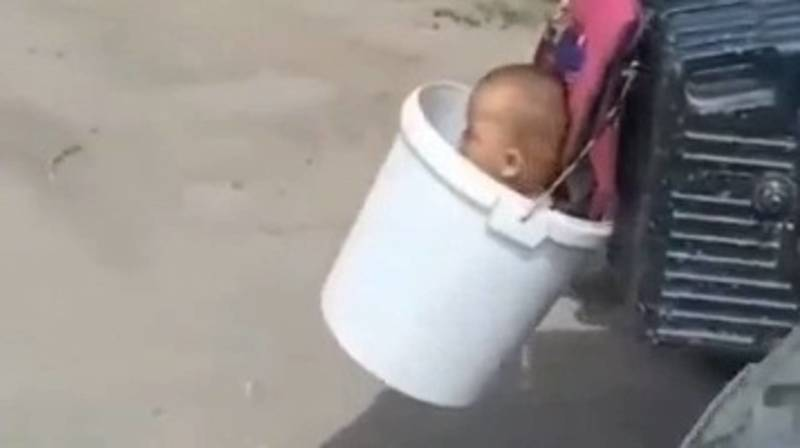 Мужчина посадил малолетнего ребенка в ведро, которое прицепил к трактору. Видео