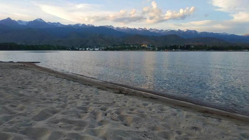 Пустынный пляж, озеро и горы. Красивый вид на Иссык-Куль. Фото