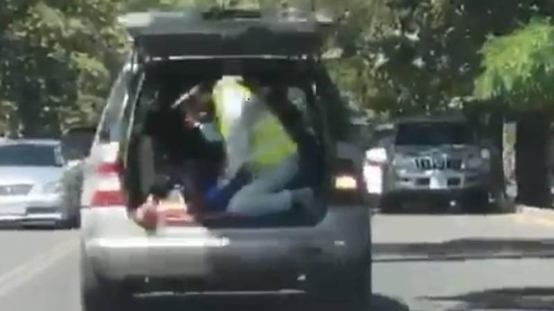 Волонтер качает кислородную подушку, пока больного везут в багажнике машины в больницу. Видео