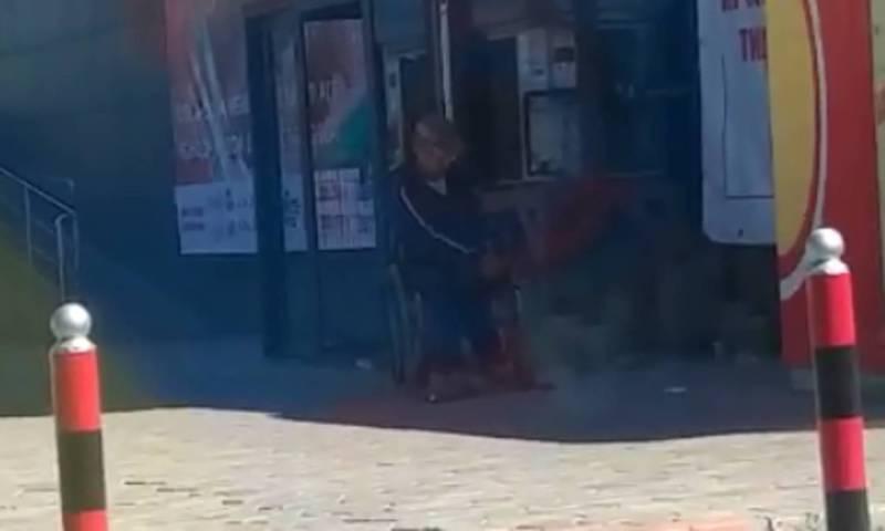 Мужчина, занимающийся попрошайничеством на инвалидной коляске, ходит