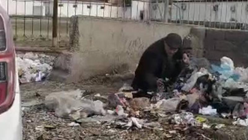 Мужчина собирает использованные одноразовые маски с мусорки. Видео
