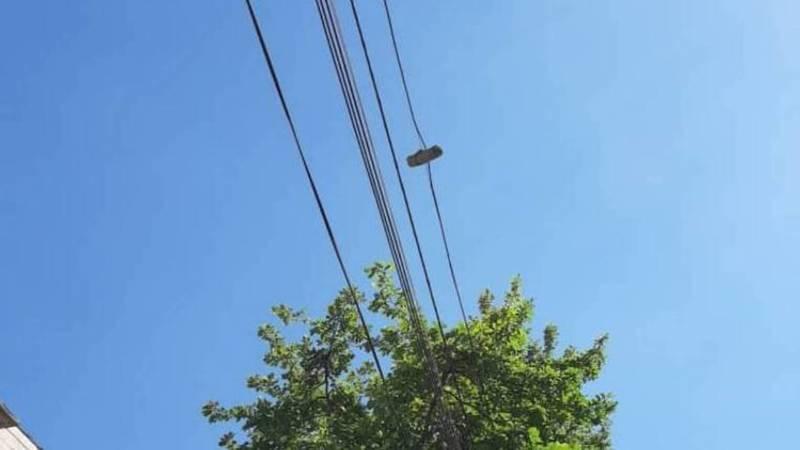На проспекте Айтматова на электропроводе висит полено, - очевидец. Фото